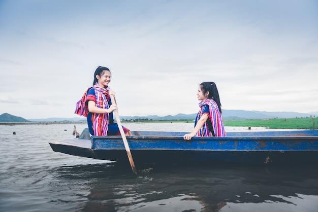 Piękne azjatyckie dziewczyny na łodzi rybackiej w jeziorze łapać ryba przy wsią tajlandia