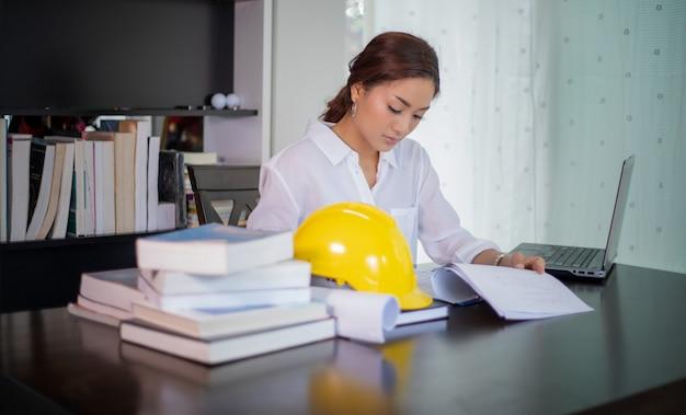 Piękne azjatyckie inżynierii kobiety sprawdza dokument i używa notatnika pracuje w domu