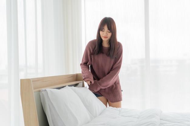 Piękne azjatyckie kobiety co łóżko w pokoju z białym czystym prześcieradłem