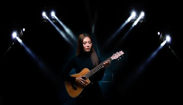 Piękne azjatyckie kobiety długie brązowe czarne włosy grać na gitarze i śpiewać piosenkę na scenie z zapaleniem dymu