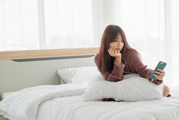 Piękne azjatyckie kobiety grające na smartfonie na łóżku