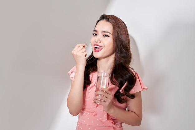 Piękne azjatyckie kobiety jedzą pigułki witaminowe dla opieki zdrowotnej w domu