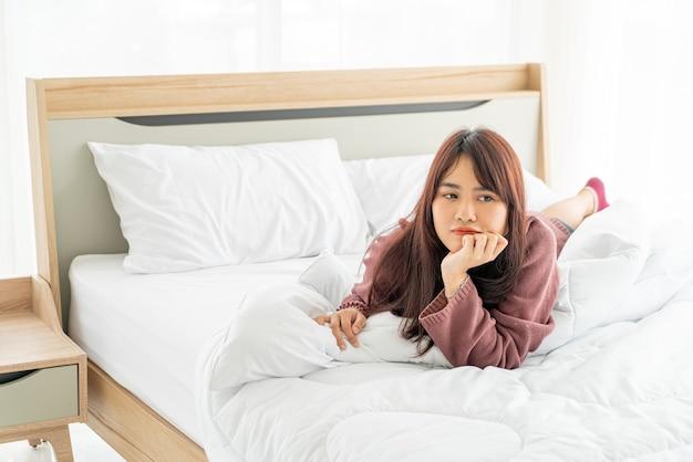 Piękne azjatyckie kobiety, leżąc na łóżku rano