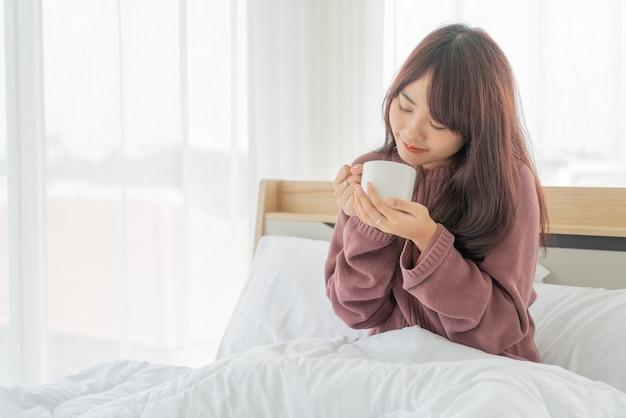 Piękne azjatyckie kobiety picia kawy na łóżku rano