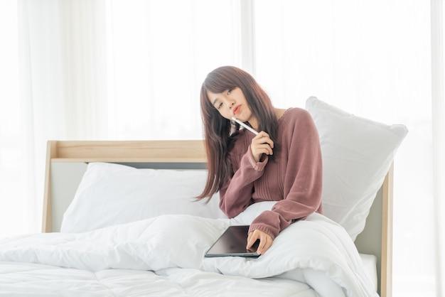 Piękne azjatyckie kobiety pracujące z tabletem na łóżku