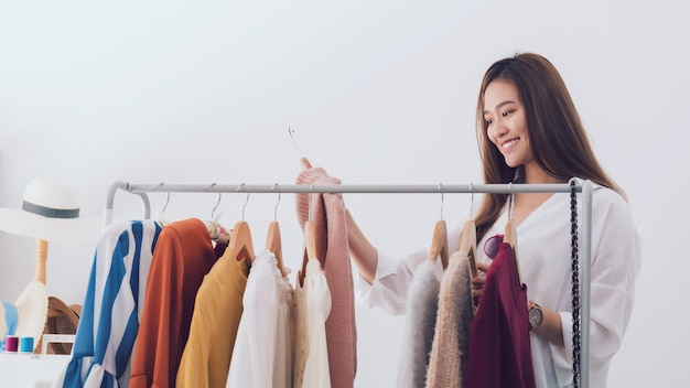 Piękne azjatyckie kobiety projektant mody stojącej w sklepie odzieżowym