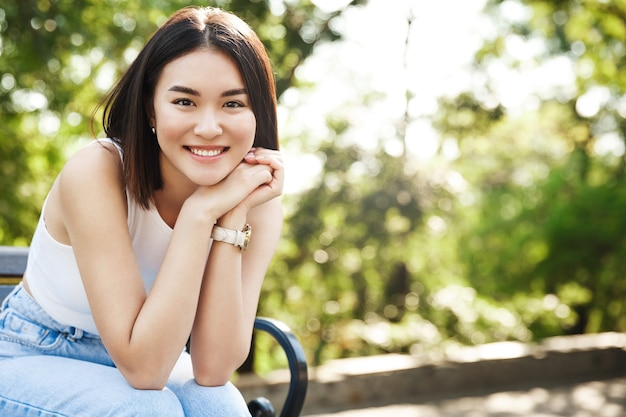 Piękne azjatyckie kobiety siedzącej na ławce i uśmiechając się