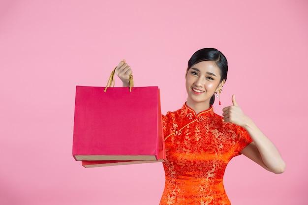 Piękne azjatyckie kobiety szczęśliwy uśmiech i zakupy w chińskim nowym roku na różowym tle.