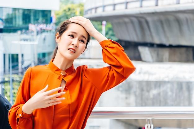 Piękne azjatyckie kobiety. tajowie noszą ubrania robocze. została uderzona i wykorzystała ręce do trzymania głowy i skręcania się tam iz powrotem z powodu upalnej letniej pogody.