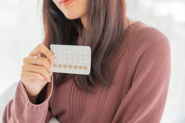 Piękne azjatyckie kobiety trzymające pigułkę antykoncepcyjną
