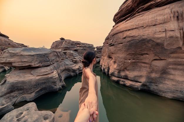 Piękne azjatyckie kobiety trzymające się za ręce z parą w skalnym wąwozie wielkiego kanionu wieczorem. sam phan bok