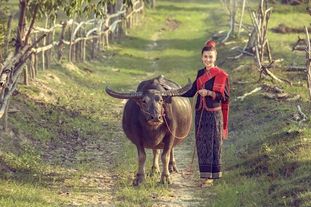 Piękne azjatyckie kobiety ubierali w krajowym kostiumu z bizonem przy ziemią uprawną.