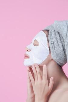 Piękne azjatyckie kobiety używają twarzy maski twarz na prześcieradle na różowym tle.