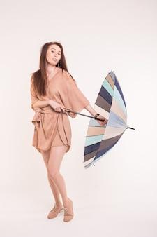 Piękne azjatyckie kobiety w sukni, otwierając parasol w białym tle