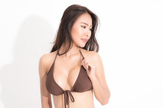 Piękne azjatyckie kobiety z długimi włosami na sobie brązową sukienkę bikini w moda lato pozowanie studio strzał na białym tle i cień.