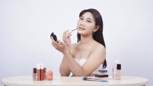 Piękne azjatyckie lusterko do makijażu na usta na białym tle