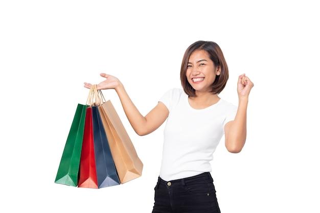 Piękne azjatyckie młoda kobieta uśmiechnięta gospodarstwa torby na zakupy na białym tle