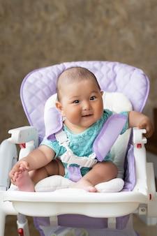 Piękne azjatyckie sześciomiesięczne dziecko siedzi na wysokim krześle