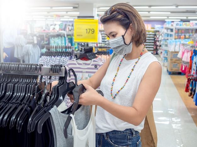 Piękne azjatykcie kobiety jest ubranym ochronnego twarzy maski zakupy w wydziałowym sklepie.