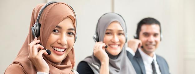Piękne azjatykcie muzułmańskie kobiety pracuje w centrum telefonicznym z drużyną, panoramiczny sztandar
