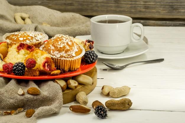 Piękne babeczki z jagodami na drewnianym stole w czerwonym talerzu