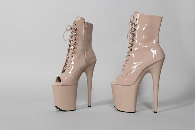 Piękne beżowe błyszczące buty do tańca na rurze lub striptizu na szarym tle