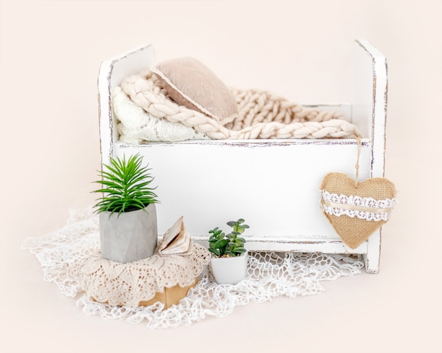 Piękne białe drewniane łóżko do sesji zdjęciowej dla noworodka z futerkiem, dekoracją poduszek. małe zaprojektowane miejsce na zdjęcie niemowlęcia na jasnoróżowym tle