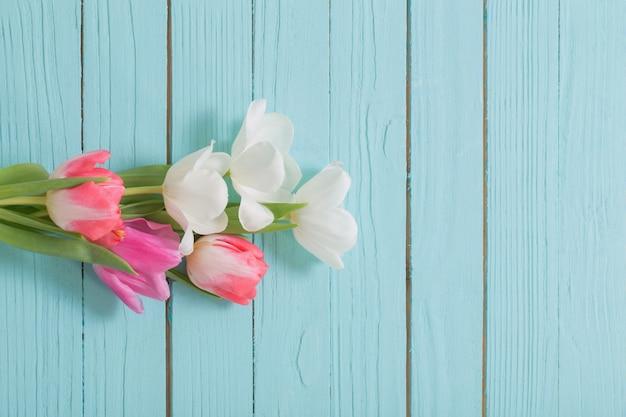Piękne białe i różowe tulipany na niebieskim tle drewnianych widok z góry