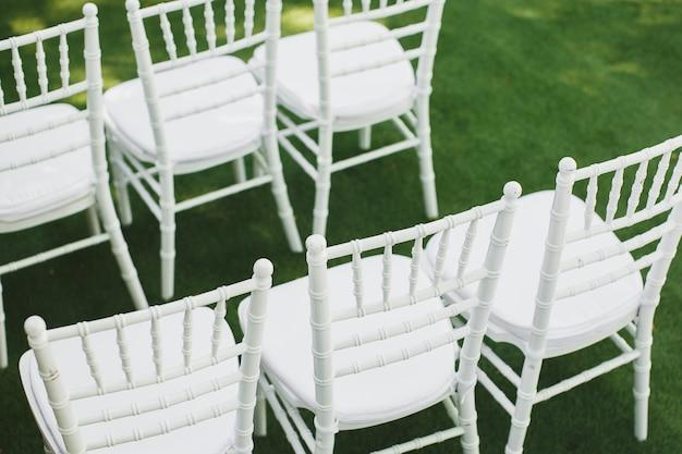 Piękne białe krzesła ślubne na ceremonii w parku.