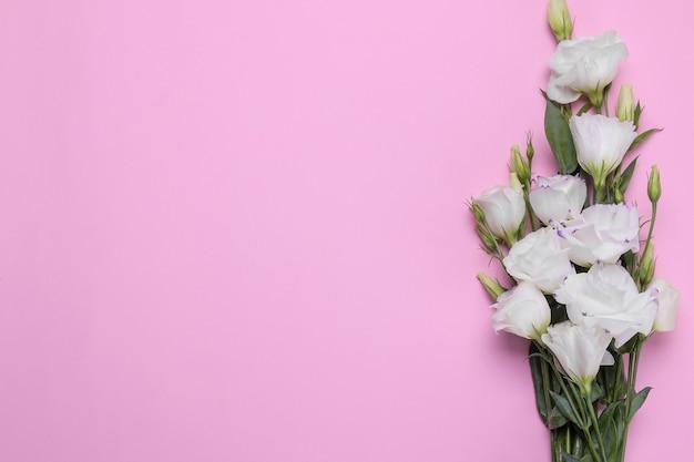 Piękne białe kwiaty eustoma bukiet na jasnym różowym tle widok z góry z miejscem na napis