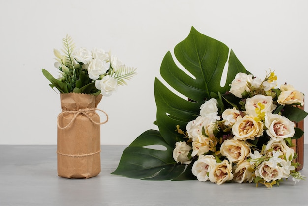 Piękne białe róże na drewnianym pudełku oraz w bukiecie na szarej powierzchni