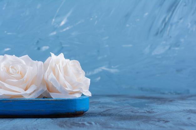 Piękne białe róże na niebieskim talerzu na niebiesko.