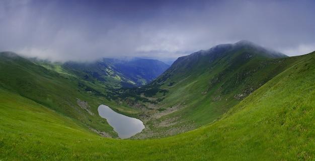 Piękne błękitne niebo i skała wysoko w karpatach. panorama jeziora