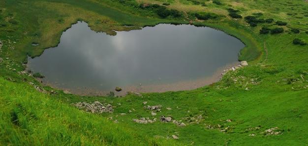 """Piękne błękitne niebo i skała wysoko w karpatach. panorama jeziora """"nesamovyte"""""""