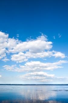 Piękne błękitne niebo pochmurne i jego odbicie w wodzie zbiornika kaniv, ukraina