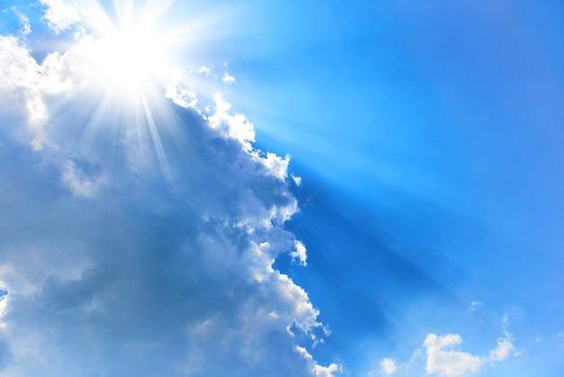 Piękne błękitne niebo z promieniami słońca i chmurami. promienie słoneczne