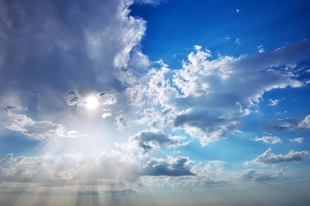 Piękne błękitne niebo z promieniami słońca i chmurami. promienie słoneczne.