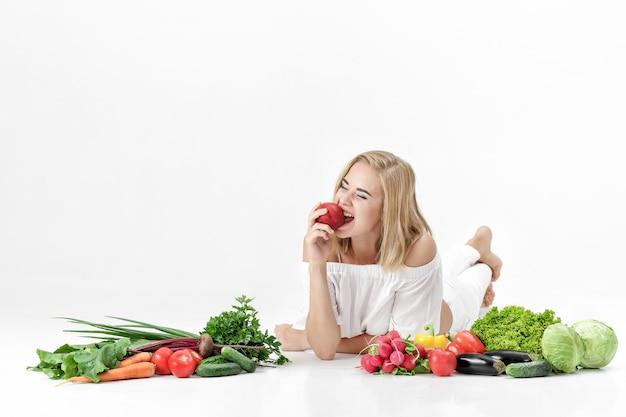 Piękne blond kobieta w białe szaty i mnóstwo świeżych warzyw na białym tle. dziewczyna je nektarynę