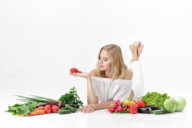 Piękne blond kobieta w białe szaty i mnóstwo świeżych warzyw na białym tle. dziewczyna trzyma pomidora