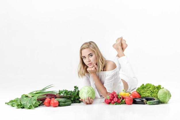 Piękne blond kobieta w białe szaty i mnóstwo świeżych warzyw na białym tle
