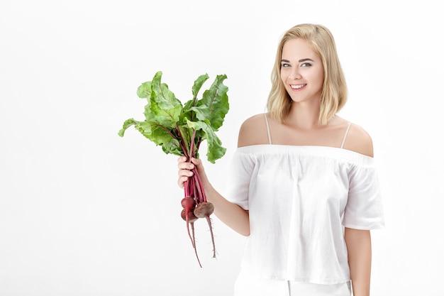 Piękne blond kobieta w białej bluzce trzyma buraka z zielonymi liśćmi na białym tle. zdrowie i witaminy