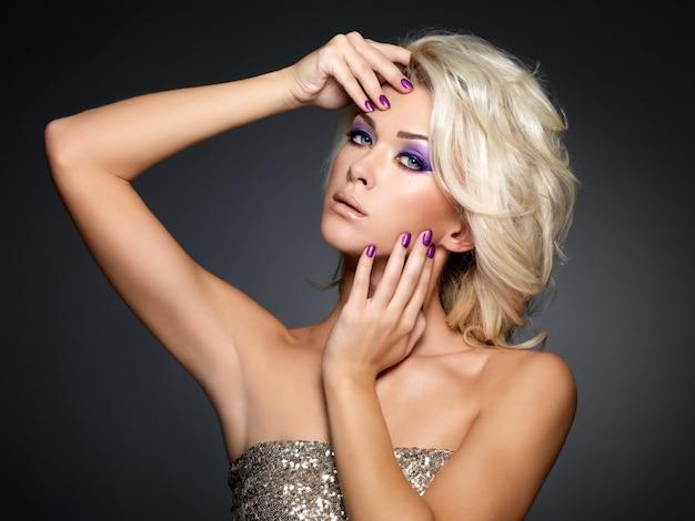 Piękne blond kobieta z uroda fioletowy manicure i makijaż oczu