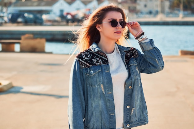 Piękne blond włosy kobieta trzyma okrągłe okulary w ręku na sobie kurtkę jeansową wygląda w lewo, letni dzień na zewnątrz w porcie