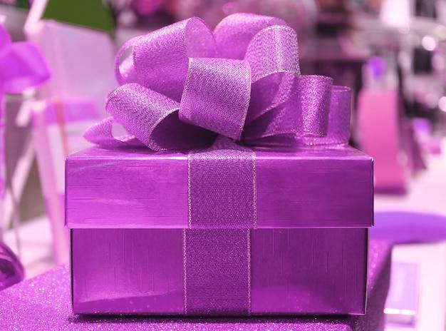 Piękne błyszczące fioletowe pudełko z kokardką z brokatowej fioletowej wstążki