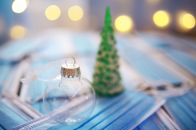 Piękne bombki świąteczne na ciemnym czarnym tle z maską medyczną. koronawirus . nowy rok na kwarantannie. projekt płaski. kopiuj miejsce. format kwadratowy. układ.