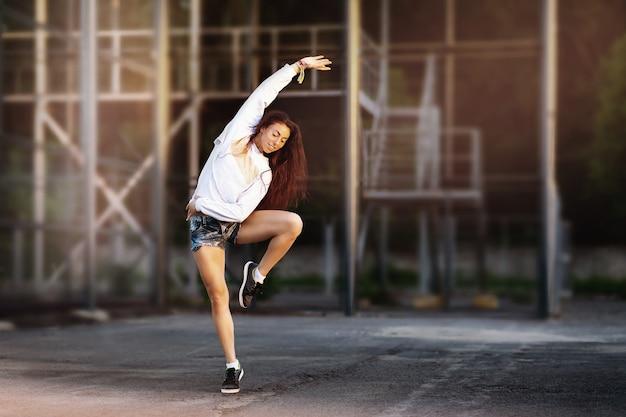 Piękne brązowowłose dziewczyna tańczy w słoneczny letni wieczór na ulicznym placu zabaw