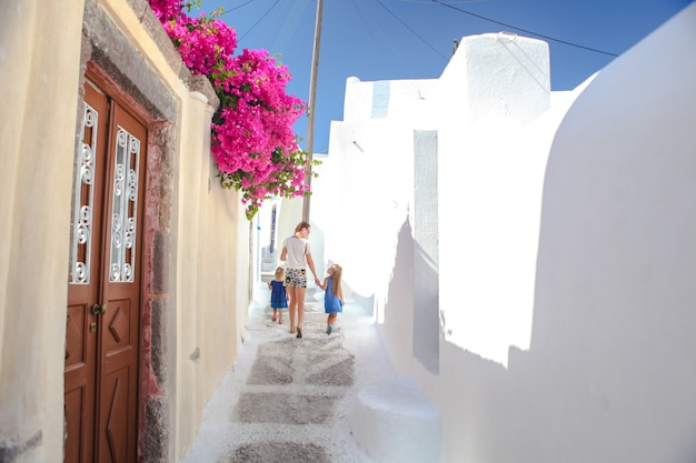 Piękne brukowane uliczki z chodzącą rodziną na starym tradycyjnym bielu domu w emporio santorini, grecja