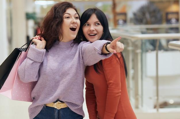 Piękne brunetki przyjaciółki zakupoholiczki wskazujące na nowy butik w centrum handlowym z sukienkami, panie wyglądające na podekscytowane, noszące swobodne swetry, pozujące z otwartymi ustami.