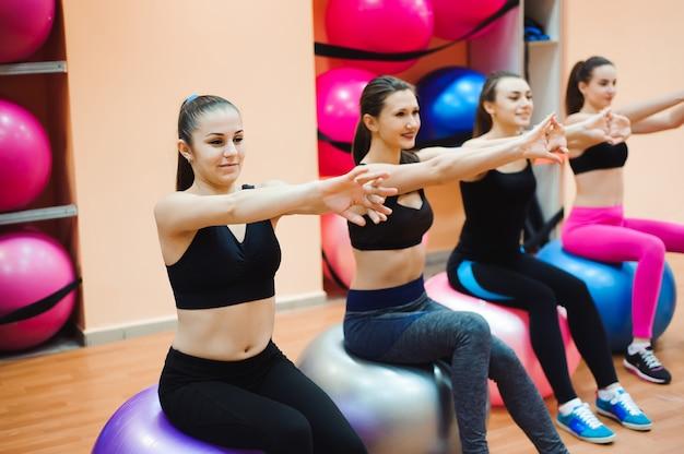 Piękne caucasian kobiety robi ćwiczeniu z gimnastyczną piłką