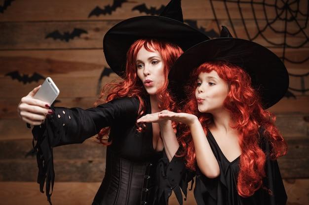 Piękne caucasian matka i córka z długimi czerwonymi włosami w kostiumach czarownic przy selfie
